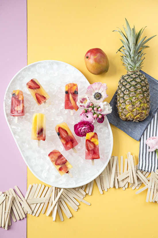 Fruit popsicles on pink and yellow background
